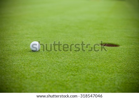 Golf ball on the green lawn in position next to hole, low depth of focus