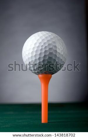 Golf Ball on the orange tee. - stock photo