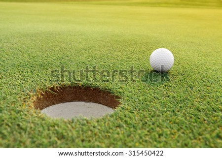 Golf ball on the pure green course - stock photo