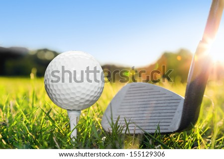 Golf ball on white tee and golf club preparing to shot. Green grass golf course. Blue sunny sky - stock photo