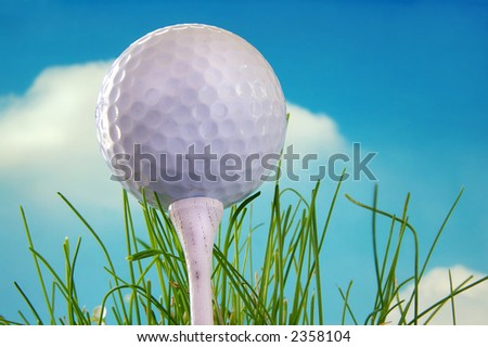 Golf ball shot from below on a tee - stock photo