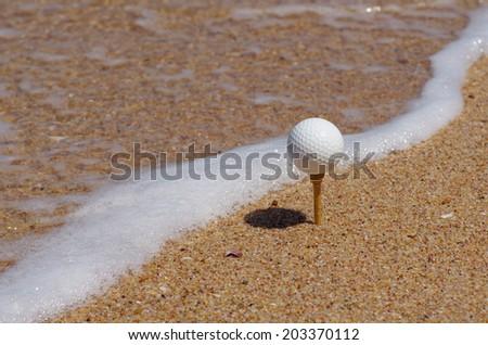 golf ball tee off on the beach. - stock photo