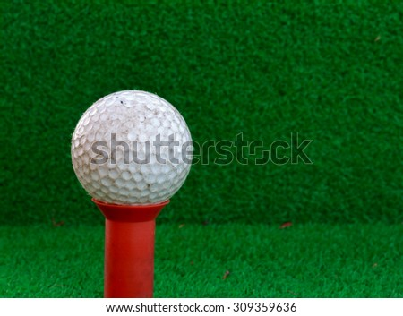 Golf ball,tee on the grass and blur background. - stock photo