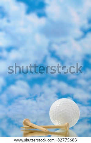 Golf ball with clouds tees and reflection - stock photo