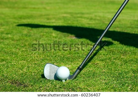 Golf ball with club and silhouette of player on the green - stock photo