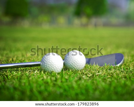 Golf ball with golf club on green glass - stock photo