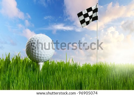 Golf ball with tee in the grass with flag against blue sky - stock photo