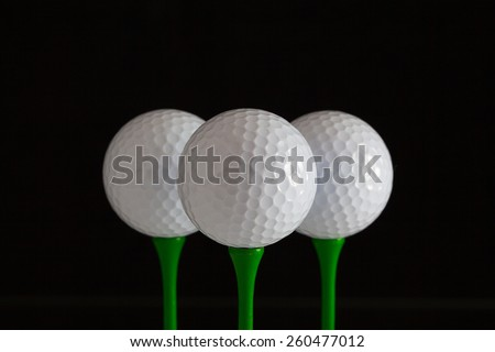 Golf balls and green wooden tees on a black background