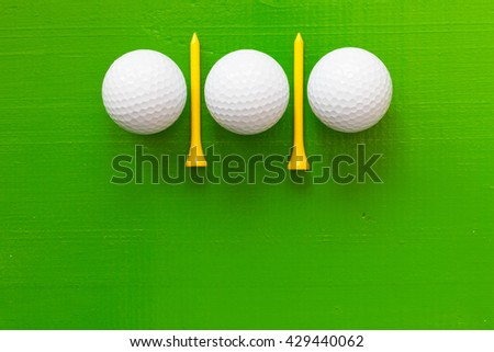 Golf balls and wooden golf tees on the wooden green table - stock photo