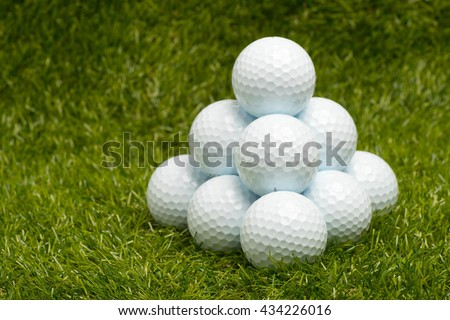 Golf balls arranged in pyramid form on green grass. - stock photo