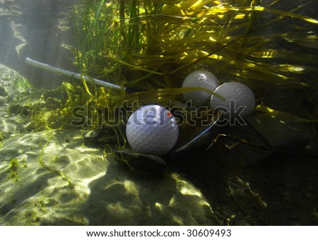Golf balls in water hazard with broken pitching wedge. - stock photo