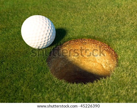 Golf balls on the grass in front of the hole. - stock photo