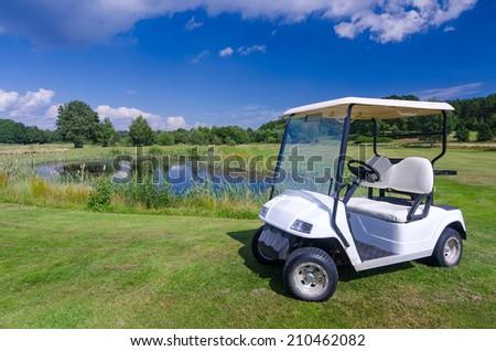 Golf car near the water pond - stock photo