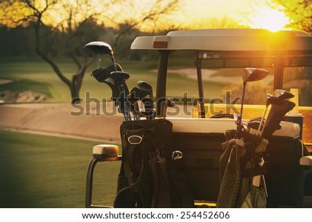 Golf cart - beautiful sunset overlooking gold course - stock photo