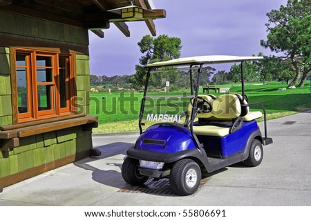 Golf cart with starter booth and golf course in background