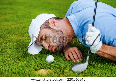 Golf cheats. Close-up of young golfer blowing at the ball while lying near the hole  - stock photo