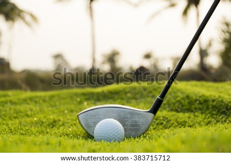 Golf club and ball in grass - stock photo
