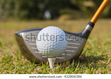 Golf club and ball in grass in at sunrise on frosty morning. at green good and beautiful golf course. - stock photo