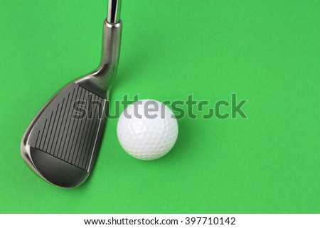 Golf club and ball on green background - stock photo