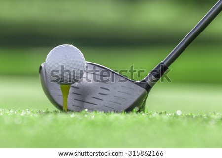 Golf club and Golf ball with tee in grass - stock photo