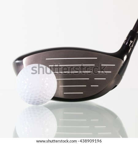 Golf club and white ball on a glass desk - stock photo