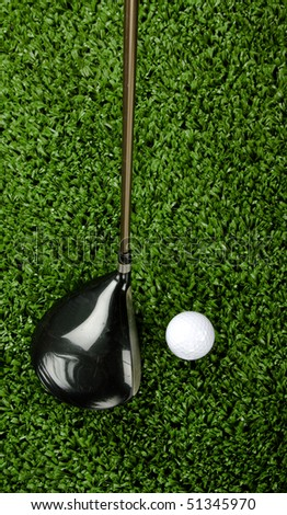 Golf club (driver) shot from above being teed up next to a white golf ball - stock photo