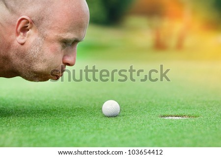 Golf club: golfer concentrating on the 18th hole - stock photo