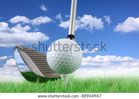 golf club with ball and tee on green in front of blue cloudy sky