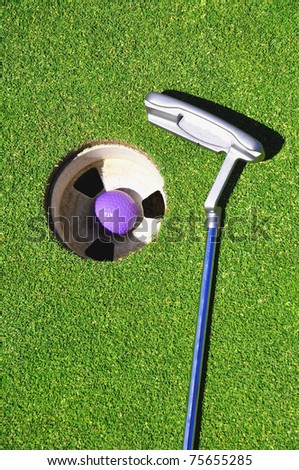 Golf club with ball in hole - stock photo