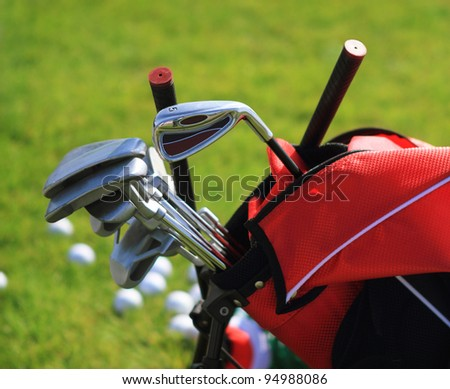 Golf clubs in golfbag and golf balls green grass background