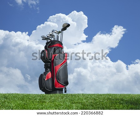 Golf clubs on grass against a blue sky and clouds - stock photo