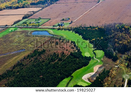 Golf course aerial photograph with farmland in the distance - stock photo