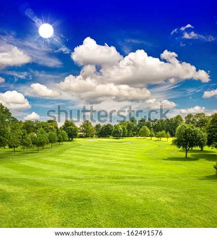 golf course and blue sunny sky. european green field landscape - stock photo