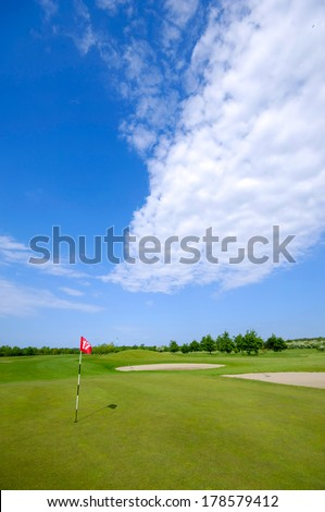 Golf course and flag. Blue and cloudy sky. - stock photo