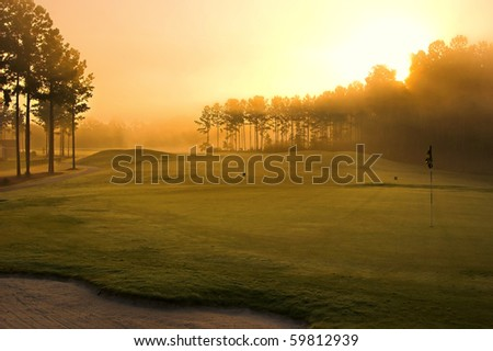 golf course at dawn backlit by rising sun - stock photo