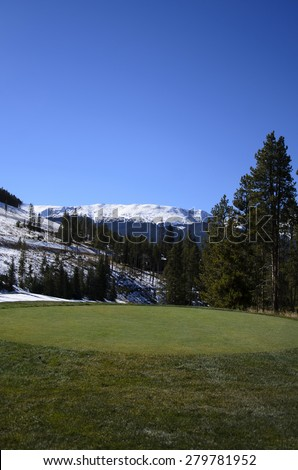 Golf course by snow covered mountains - stock photo
