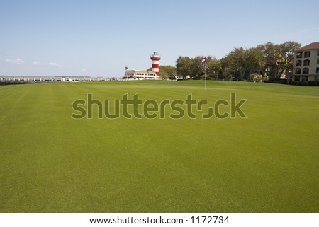 Golf course green overlooking the ocean - stock photo