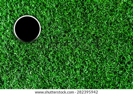 Golf course hole with artificial grass. - stock photo