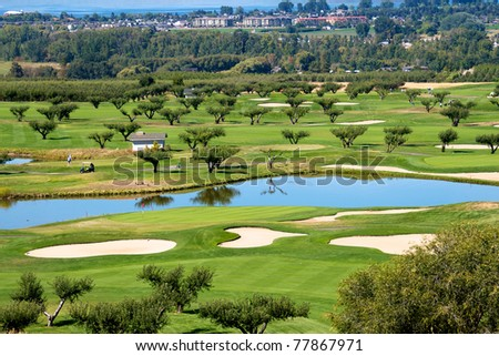 Golf course in the Okanagan valley set among vineyards and apple orchards with a backdrop of lake Okanagan - stock photo