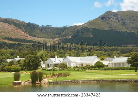 Golf course landscape with few houses in the mountains on a beautiful summer day - stock photo