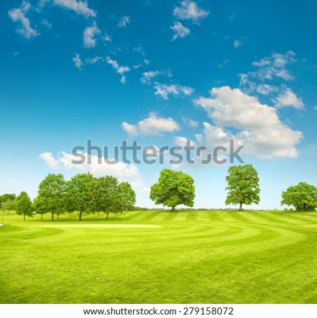 Golf course. Spring field with green grass, trees and cloudy blue sky - stock photo