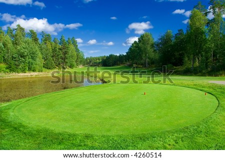 Golf course with a pond - stock photo