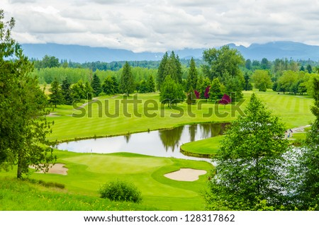 Golf course with gorgeous green and pond. - stock photo