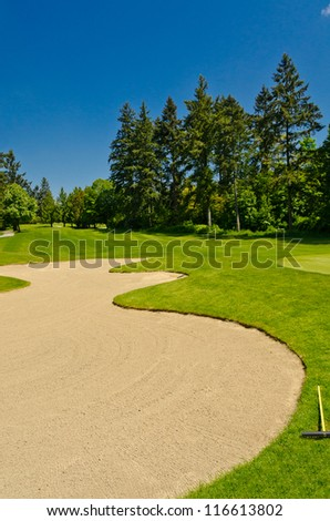 Golf course with gorgeous green and sand bunker. - stock photo