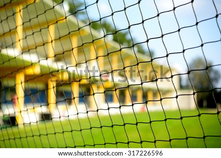 Golf driving range from behind protective net. Selective focus on net with blurred background of driving range. - stock photo