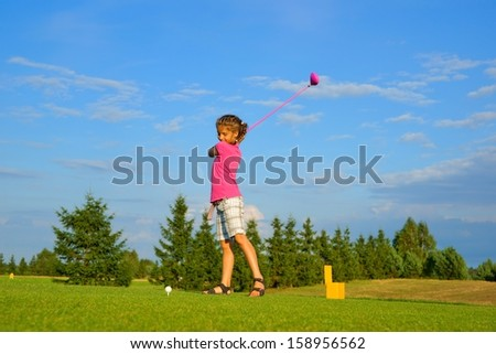 Golf, girl golfer is going to punch the ball - stock photo