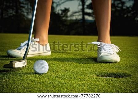 golf girl putting at green - stock photo