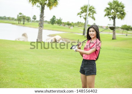 Golf girl with driver at green