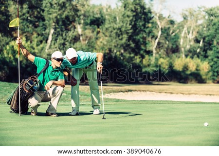 Golf. Golfer reading the green with his caddy - stock photo