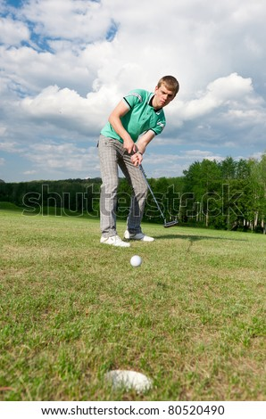 Golf green hole course man putting ball inside short putt - stock photo
